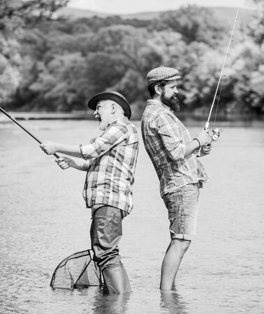 generations. summer weekend. mature men fisher. male friendship. family bonding. hobby and sport activity. Trout bait. father and son fishing. two happy fisherman with fishing rod and net