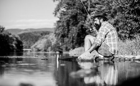 Man catching fish. Man at riverside enjoy peaceful idyllic landscape while fishing. Guy fly fishing. Successful fly fishing. Hobby for soul. United with nature. Fisherman fishing technique use rod