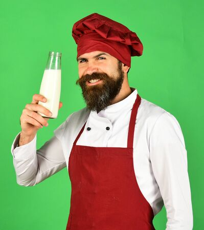 Man with beard holds glass bottle on green background.