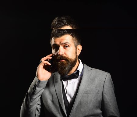 Business and appointment concept. Man with long beard holds phone