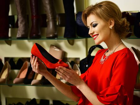 Girl with makeup looks at high heeled shoe.