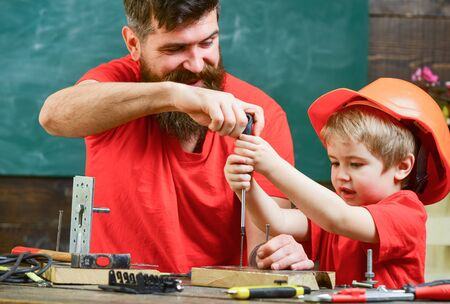 Boy, child busy in protective helmet learning to use screwdriver with dad. Father, parent with beard teaching little son to use tool screwdriver. Teamwork and assistance concept.