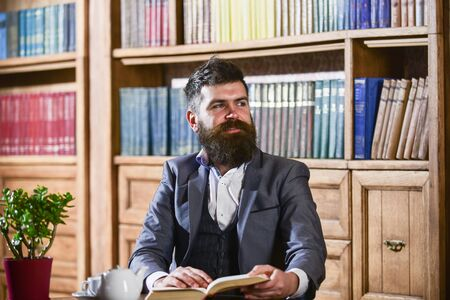 Aristocrat on smiling face holds book. Man in classic suit
