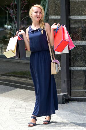 Shopping concept. Woman in black dress with bags