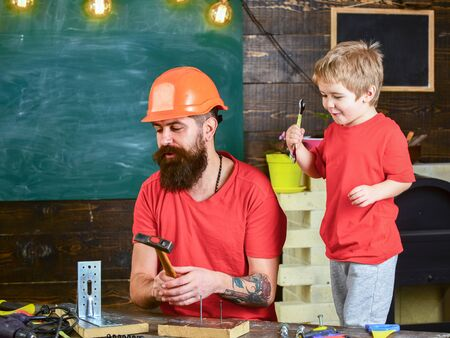 Boy, child cheerful playing and learning to use tools with dad. Fatherhood concept. Father, parent with beard in protective helmet teaching little son to use different tools in school workshop Stok Fotoğraf