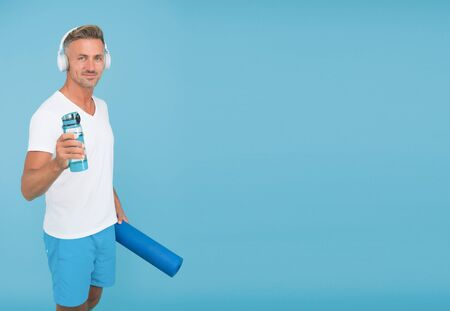 Health and energy. Healthy athlete hold water for yoga training. Fitness coach blue background. Water and hydration. Health benefits. Water balance and health. Improve your health, copy space 版權商用圖片