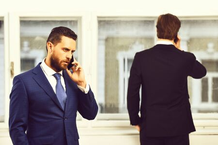 serious men or businessmen speaking on mobile or cell phone