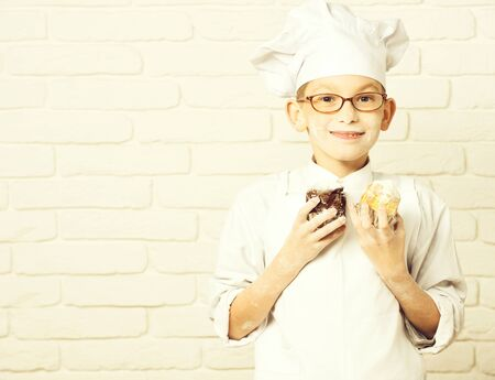 stained cute cook chef boy on brick wall background, copy space