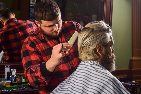 Barber hairstyle barbershop. Hipster getting haircut. Sharp object near face and squirming distracts person holding it. Donate hair. Donation and charity concept. Guy with dyed blond hair. Cut hair.
