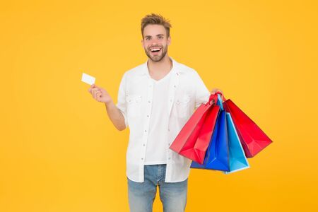Bachelors day. Consumerism concept. Cheerful client customer consumer smiling with fashion purchases. Impulse purchases. Big discount. Happy man holding purchases in paper bags. If I want I will get Archivio Fotografico