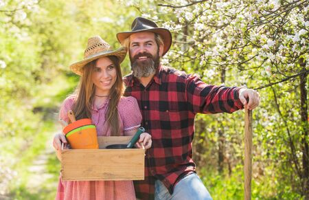 Organic farm. Smiling couple in love gardening. Girl hold box with pots and tools. Farming season. Happy couple ranch owners. Ecology environment. Soils and fertilizers. Planting plants. Family farm