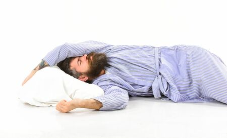 Man with sleepy face lies on pillow, sleeps. Hipster with beard and mustache sleeping. Man in bathrobe sleep, nap, rest, relax, white background. Quality of sleep concept.