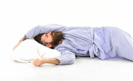 L'homme au visage endormi est allongé sur un oreiller, dort. Hipster avec barbe et moustache dormant. Homme en peignoir, sommeil, sieste, repos, détente, fond blanc. Concept de qualité du sommeil.