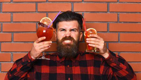 Brutal man with long beard holds bar cocktails.