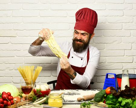 Chef makes dough. Man with beard stretches kneaded dough