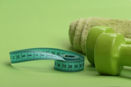 Healthy regime equipment. Dumbbells in green color, twisted measure tape and towel on green background, defocused. Athletics and weight loss concept. Tape measure in cyan color by barbells, close up