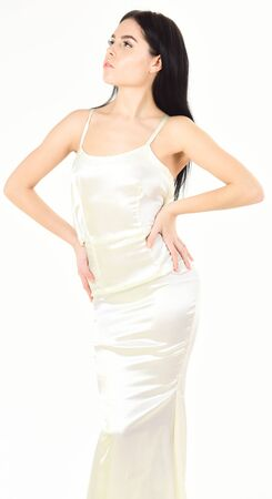 Lady on calm face wears expensive fashionable evening dress. Slim and fit concept. Fashion model with slim figure as result of dieting and fitness. Woman in elegant white dress, white background. Stockfoto