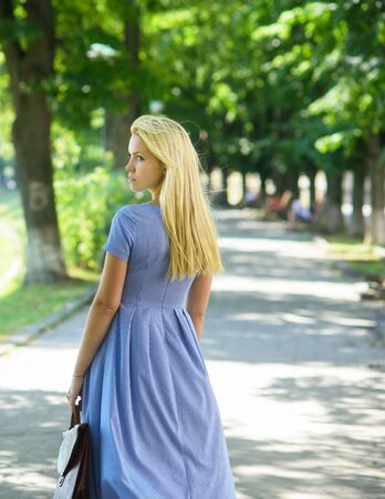 Girl with long blonde hair wears blue dress walking 免版税图像