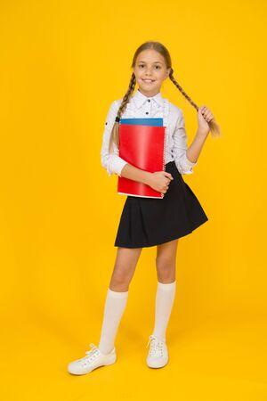 Cute schoolgirl. School education. Courses for gifted children. Basic level. Happy schoolgirl hold textbooks yellow background. Little schoolgirl back to school. Small schoolgirl wear uniform Banque d'images