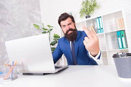 Fuckoff oclock. Businessman show middle finger working in office. Obscene hand gesture. Nonverbal communication. Aggressive working conditions. Working in stressful environment. Busy working day Standard-Bild