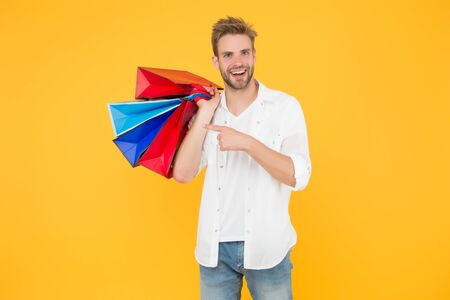 Big discount. Happy man holding purchases in paper bags. If I want I will get. Bachelors day. Consumerism concept. Cheerful client customer consumer smiling with fashion purchases. Impulse purchases Stok Fotoğraf