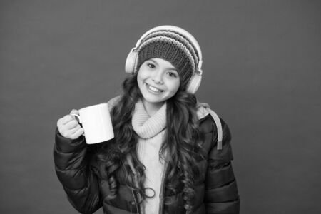 Weekend begins like that. Hipster fashion trend. Winter holidays activity. Feeling warm and happy. Cheerful smiling child stylish outfit listen music. Listening music and drinking cocoa. Music taste
