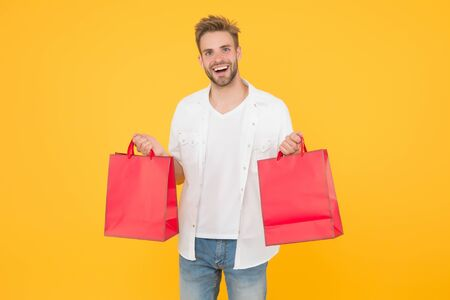 If I want I will get. Bachelors day. Consumerism concept. Cheerful client customer consumer smiling with fashion purchases. Impulse purchases. Big discount. Happy man holding purchases in paper bags
