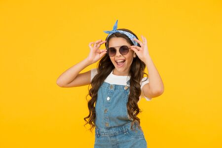 Enjoying new great day. happy childrens day. cheerful vintage girl on yellow background. little beauty at hairdresser. love her retro fashion style. summer vacation. summer shopping sales. pin up kid