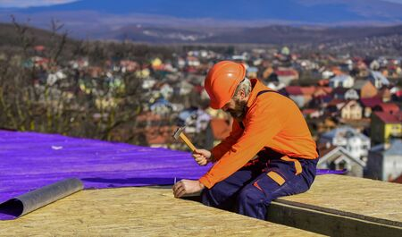 Roofer constructing new roof. Builder roofing surface. Professional master repair roof. Flat roof installation. Construction building. Waterproof sheet materials. High altitude works. Heat insulation. 免版税图像