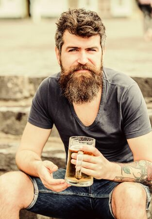 Cafe summer terrace. Light ales or dark stouts drink them all. Man with beard and mustache hold beer glass outdoors. Guy having rest with cold draught beer. Hipster relaxed drinking beer outdoor