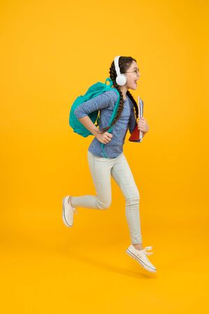 Full of energy. Energetic child run to school. Happy girl in motion yellow background. Childhood energy. Maintaining kinetic energy. School and education. Active learning. Being in positive energy Stock fotó
