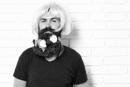 hipster with flowers in beard on white brick wall background