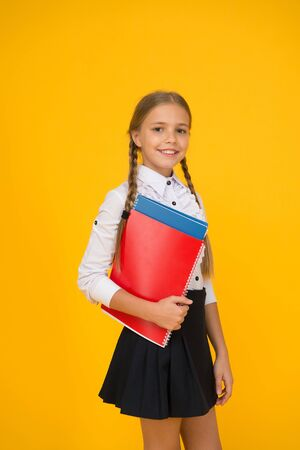 Basic level. Happy schoolgirl hold textbooks yellow background. Little schoolgirl back to school. Small schoolgirl wear uniform. Cute schoolgirl. School education. Courses for gifted children