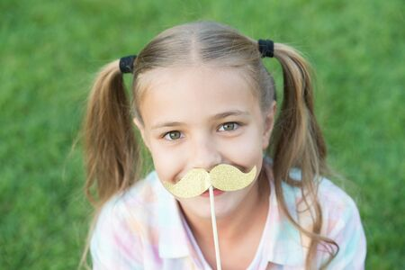 All the taste of being a girl. Happy girl hold fake mustache outdoors. Child girl with party props. Small girl wear long hair tails. Summer fun. Beauty look. Hair salon. Childhood and girlhood Stockfoto