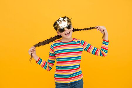 Your inner queen. Happy princess hold hair yellow background. Small child wear prop crown and glasses. Party girl with long hair. Kids barber. Hair salon. Haircare products. My hair my look