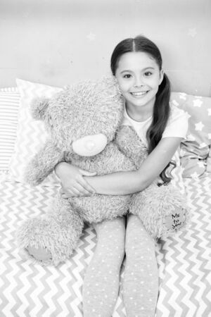 My best friend. Favorite toy. Girl child hug teddy bear in her bedroom. Pleasant time in cozy bedroom. Girl kid long hair cute pajamas relax and play plush teddy bear toy. Pure love concept