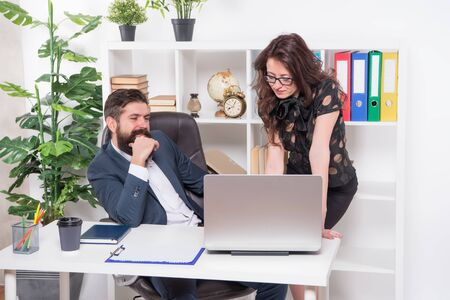New ways to automate business processes. Managers work in modern office. Bearded man and sexy woman use laptop. Using modern computer technologies. Running modern business. Modern life