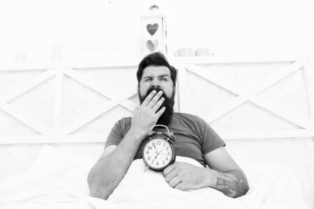 Stressed man yawning takes alarm clock. Too early. Sleepy man holding alarm clock in bed. Bearded man yawning with alarm clock. Sleep longer. hipster want to sleep. the morning time. its bachelor day