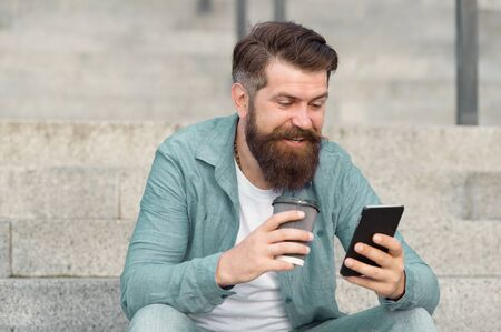 Got SMS online. Happy man read SMS drinking coffee outdoors. Sending and receiving SMS via smartphone. Mobile communication. SMS messaging. Short message service. New technology. Modern life. 3G. 4G