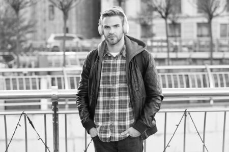 Podcast for youth. Online education courses. Listen music. Tourist hipster with backpack headphones. Self improve. Handsome man enjoy music urban background. Distance education. Modern education