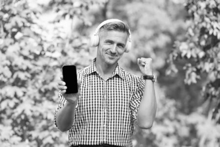 Mobile music. Happy man listen to music in headphone. Modern life. Mobile technology. Mobile lifestyle. Enjoy music playing in mobile phone Reklamní fotografie
