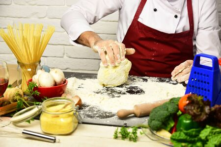 Male hands work with kneaded dough on white brick wall background. Chef makes dough. Cook in burgundy uniform sits by table with vegetables and kitchenware. Professional cookery concept.