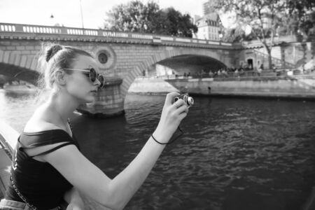 Best camera for tourists. Pretty photographer take photo of city river.  girl shoot with camera. Compact travel camera. Camera for shooting travel photography on vacation. Travelling and vacation Archivio Fotografico