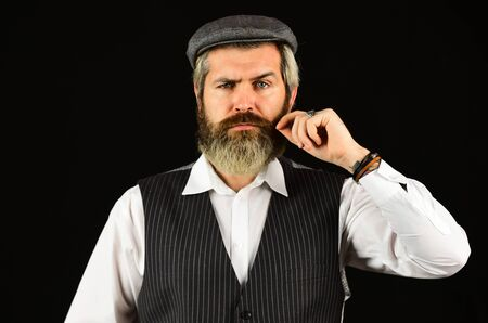 Retro gentlemen. Mature handsome man. Man in vintage style hat. Brutal bearded hipster vest. Old fashioned. Real masculinity. Masculine appearance. Bearded guy on black background. Beard grooming