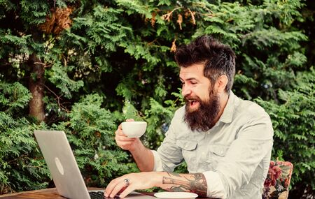 Offsite work. Hipster drinking tea and using computer work station outdoor. Bearded man doing his work online. Working globally through distance work Stockfoto