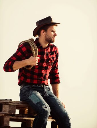 any way possible. cowboy with lasso rope. Western. western cowboy portrait. man checkered shirt on ranch. wild west rodeo. Thoughtful man in hat relax. Vintage style man. Wild West retro cowboy