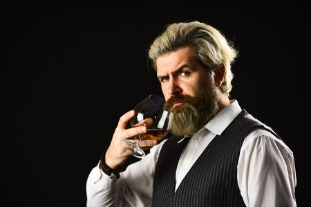 Good indication of condition of whisky. Bearded businessman in elegant suit with glass of whisky. Sommelier tastes expensive drink. Elegant macho drink cognac. Matured in sherry casks. Whisky tasting