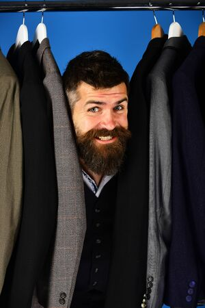 Tailor with happy face near custom jackets on blue background Stok Fotoğraf