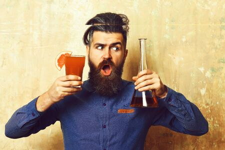 Brutal hipster holding alcoholic shot and glass tube or flask