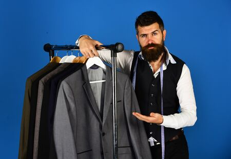 Designer presents suit near clothes hangers. Man with beard Stok Fotoğraf